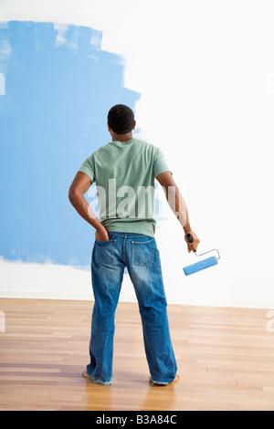 African American jeune homme debout à côté de la moitié mur peint avec rouleau à peindre Banque D'Images