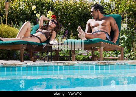 Multi-ethnic couple de détente près de la piscine Banque D'Images