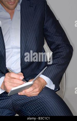 Un homme d'écrit dans un bloc-notes Banque D'Images