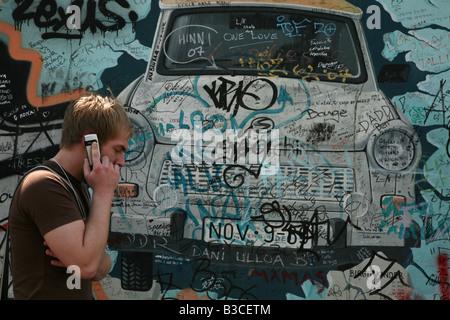 Homme avec un téléphone cellulaire en passant par la Trabant briser le mur sur la photo du mur de Berlin à Berlin, Banque D'Images