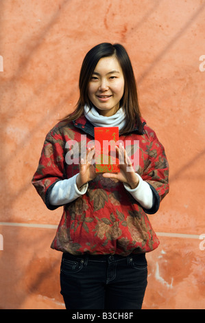 La Chine, Beijing. Une jeune Chinoise portant des vêtements de style chinois traditionnel tenant une enveloppe Hongbao Banque D'Images