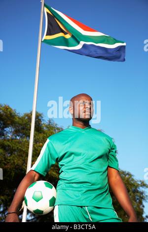 13MA-023 © Collection aFRIKA Monkeyapple Grand Stock! Joueur de football posant avec boule sous drapeau sud-africain Banque D'Images