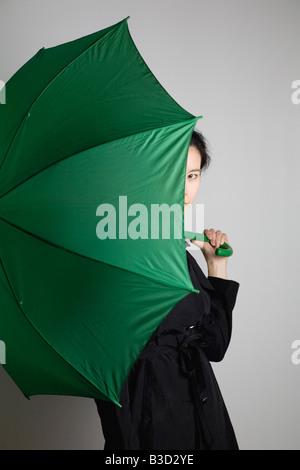 Jeune femme debout avec parapluie, portrait Banque D'Images
