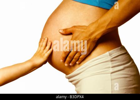 Ventre de femme enceinte avec des mains de bébé Banque D'Images