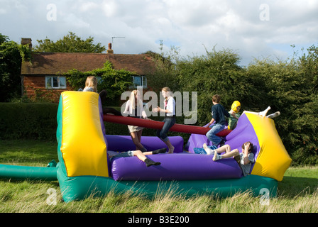 Adolescents jouant sur un château gonflable gonflable outdoor party Banque D'Images