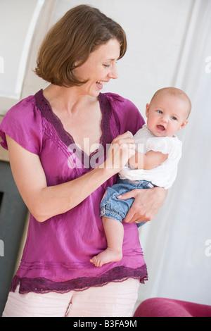 Mère dans la salle de séjour holding baby smiling Banque D'Images