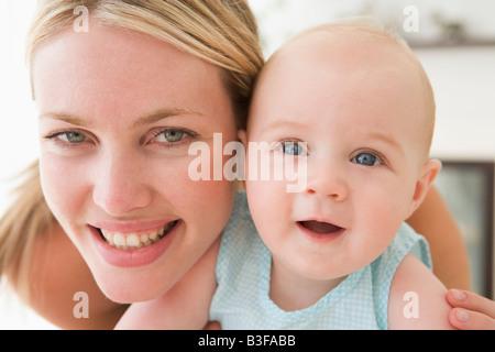 Mère en salon avec baby smiling Banque D'Images