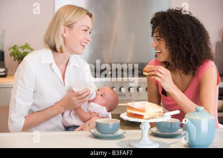 Mère et bébé en cuisine avec ami eating cake and smiling Banque D'Images