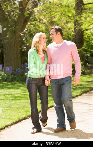 Couple walking on path smiling holding hands Banque D'Images