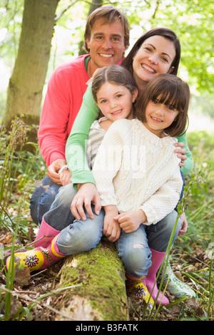 Famille en plein air dans les bois assis sur log smiling Banque D'Images
