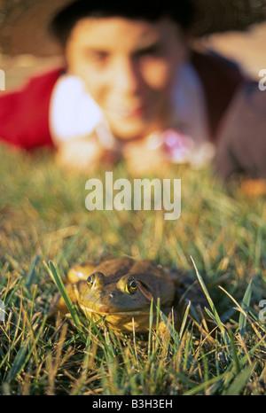Un jeune garçon hisr entraîneurs grenouille dans un concours de saut de grenouille à l'assemblée annuelle Tom Sawyer Banque D'Images