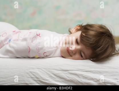 Petite fille aux yeux clos, au lit et sourire Banque D'Images