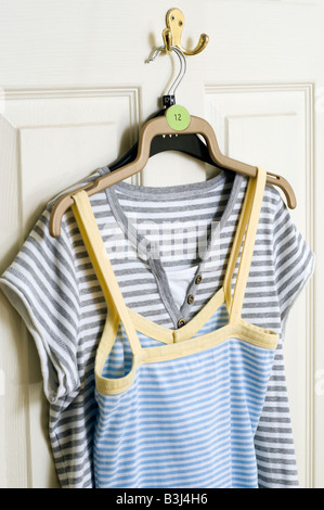 Deux dames taille 12 été 'tee-shirts 'accroché à un crochet à l'arrière d'une porte blanche Banque D'Images
