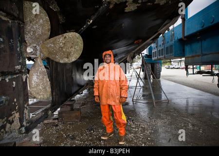 Pression de Robert Palmer lave le fond d'un bateau de pêche de 88 pieds de long Be3 au chantier à Port Townsend Banque D'Images