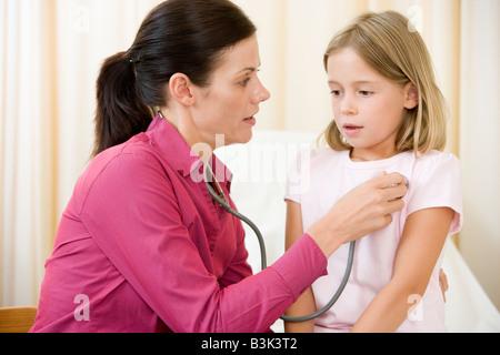 Doctor giving checkup avec stéthoscope pour jeune fille dans la salle d'examen Banque D'Images