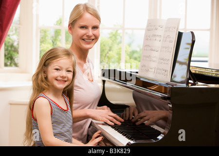 Woman and young girl playing piano and smiling Banque D'Images