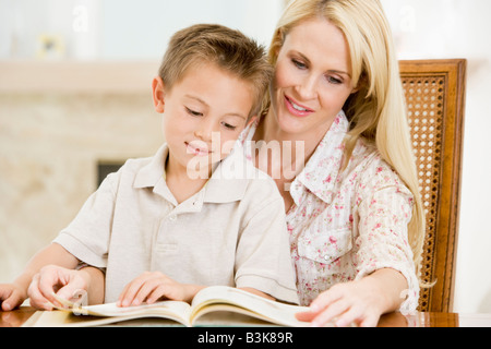 Woman and young boy reading book in dining room smiling Banque D'Images