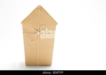 Studio Shot of Model House enveloppé dans du papier brun et liés avec de la ficelle Banque D'Images