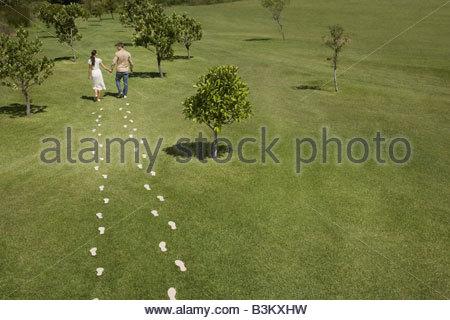 Couple en train de marcher à travers l'empreinte de pied sur le terrain Banque D'Images