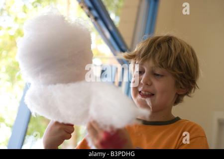 Un garçon de neuf ans avec grande boule de coton douce candy Banque D'Images