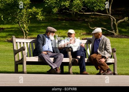 Regent's Park Gardens , scène de trois très vieux hommes assis sur un banc d'avoir un débat animé et profiter du Banque D'Images