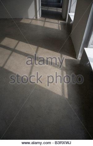 La lumière du soleil brillant à travers une fenêtre sur un sol en béton lisse Banque D'Images