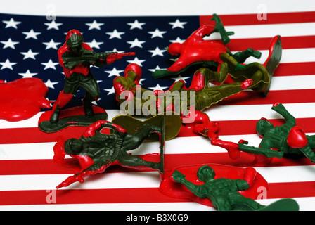 Une photo montrant conceptuel soldats jouets dans une mare de sang couché sur un drapeau américain Banque D'Images