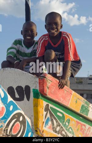 Deux jeunes garçons sénégalais jouant sur la proue d'un bateau à Dakar, Sénégal. Banque D'Images
