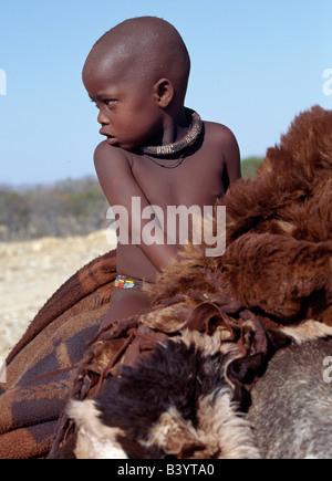La Namibie, Kaokoland, Opuwo. Un jeune garçon Himba rides accueil confortablement sur un âne. Aviateur et couvertures prendre sa selle. Son corps est enduit d'un mélange d'ocre rouge, de la matière grasse et les herbes. Déjà il porte un collier de perles blanc traditionnel, appelé ombwari, qui va devenir plus gros et plus lourd qu'il vieillit.Les Himbas Herero Bantu francophone sont des nomades qui vivent dans les conditions difficiles, sec mais très beau paysage de la nord-ouest de la Namibie.