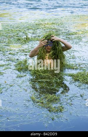 Un jeune garçon jusqu'à sa taille en lui-même couvre la rivière dans la lutte contre les mauvaises herbes au cours Banque D'Images