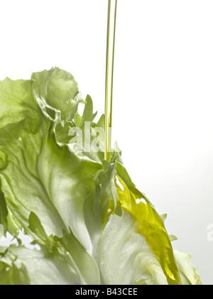 Verser une goutte d'huile d'olive sur une feuille de laitue Banque D'Images