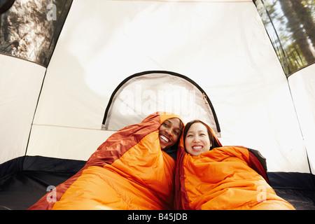 Multi-ethnic couple à l'intérieur de sacs de couchage et de tente Banque D'Images