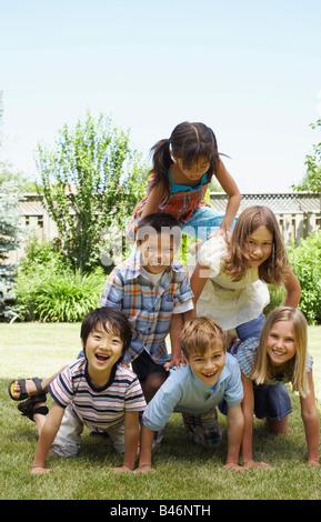 Groupe d'enfants formant pyramide humaine en plein air