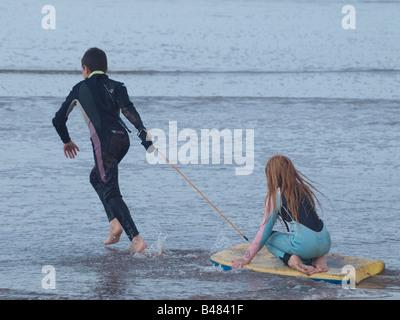 Garçon Fille tirant sur le bodyboard en eau peu profonde à la plage Banque D'Images