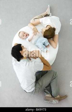 Les parents et le bébé se détendre sur un pouf, baby holding mother's hand, overhead view