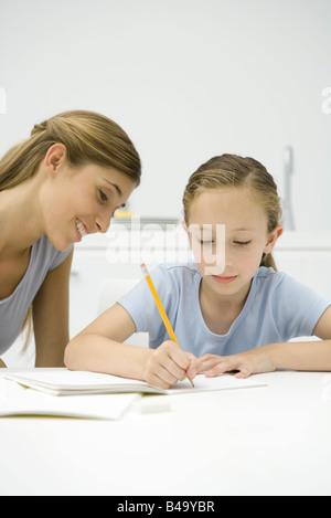 Girl doing homework at table, mère regardant Banque D'Images