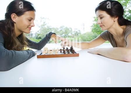 Deux femmes jouant aux échecs, l'un faisant un mouvement, l'autre effleurant sa main Banque D'Images