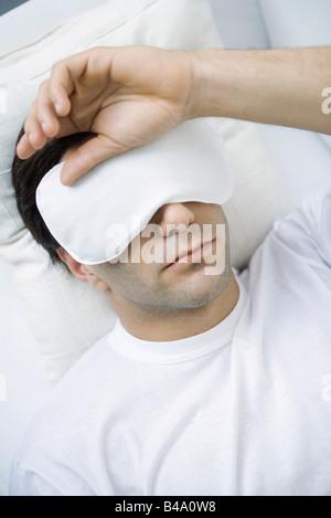 Homme couché avec un masque pour les yeux, la main sur la tête Banque D'Images