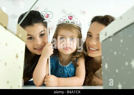 Petite fille avec mère et sa sœur, habillée en princesse, les cadeaux d'anniversaire en premier plan Banque D'Images