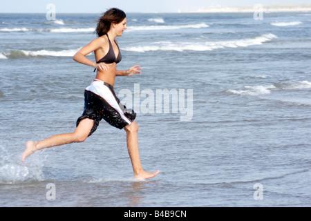 Les jeunes adolescents d'une femme fille courir pieds nus plage mer eau peu profonde de tout le corps de sable maillot Banque D'Images