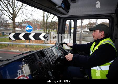 Porter un haut-vis tabard et une casquette, un jeune conducteur est assis au volant de son camion poids lourds sur Banque D'Images