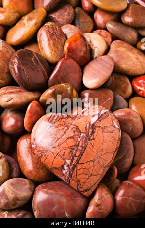 Pierre en forme de coeur sur le lit d'autres roches Banque D'Images