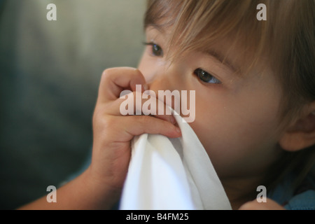 A 23 mois bébé fille suce son pouce en tenant un tshirt blanc uni et qu'elle utilise comme une couverture de sécurité. Banque D'Images