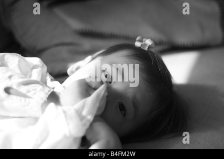 A 17 mois bébé fille suce son pouce en fixant au soleil sur une table. Banque D'Images