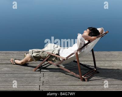 Un jeune homme assis dans une chaise longue sur une jetée Banque D'Images