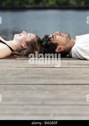 Un jeune couple couché sur une jetée tête à tête de Banque D'Images