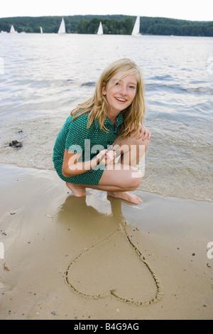 Une jeune fille dessinant un coeur dans le sable à la plage Banque D'Images