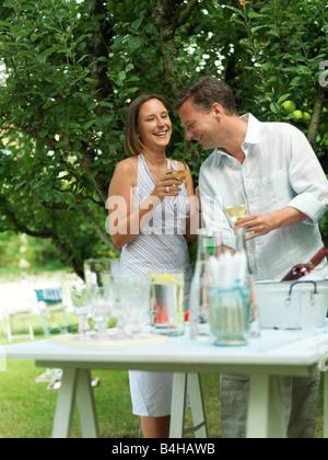 Couple holding verres de vin et smiling in garden Banque D'Images