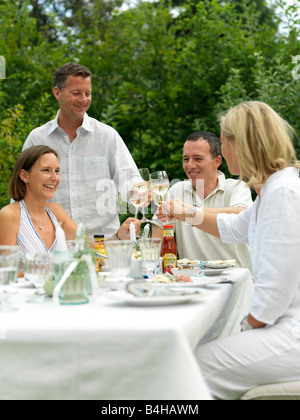 Deux couples toasting with wine glasses at a garden party Banque D'Images