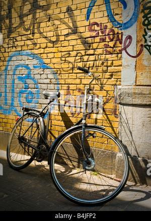 Un ancien et traditionnel néerlandais rouille location appuyé contre un mur jaune couvert de graffitis à La Haye, Banque D'Images